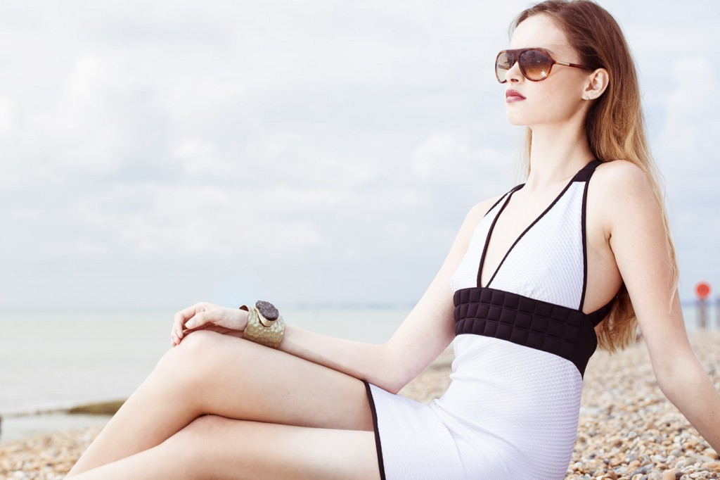 Photo: Brighton Beach location beauty fashion photo-shoot, designer swimwear, imagery by fashion campaign photographer Margaret Yescombe, model Tamara Milk Management, Swimwear by Sumarie, MUA/Hairstylist Christiana Howell, earrings model's own. Creative Director, Photographer, Retoucher: Margaret Yescombe Photography London, white swimsuit with black bow detail, accessories Versace designer sunglasses