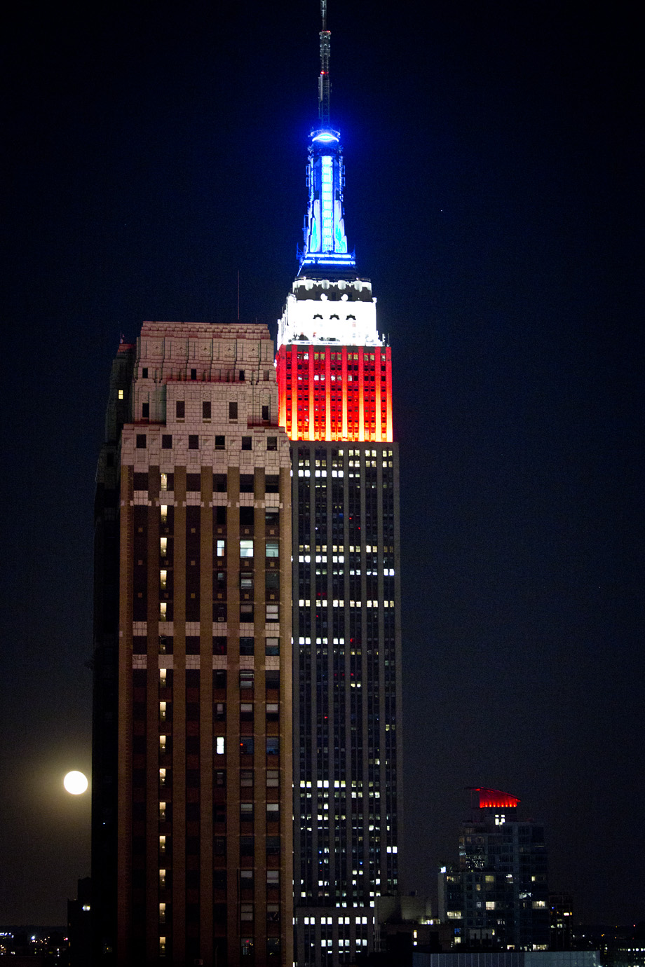 Empire States Building lit up at night red white and blue colours with the moon in the dark sky